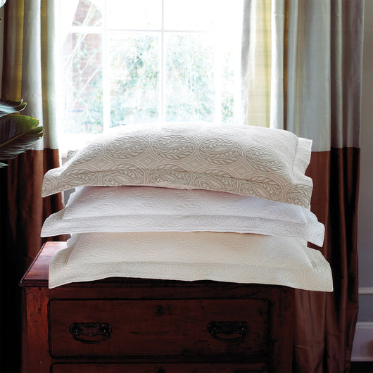 Stack of French medallion matelasse shams sitting on a bedside table