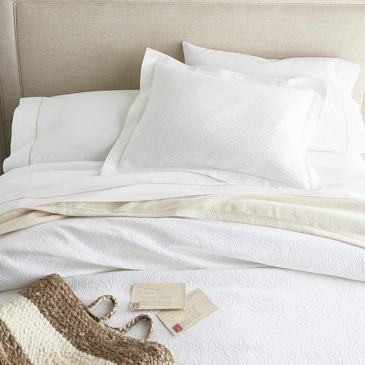 White bed with French medallion matelasse coverlet and shams