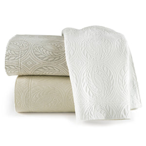 Stack of folded Vienna coverlets in white, linen and ivory