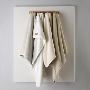Cotton fleece-like blankets hanging from a wall