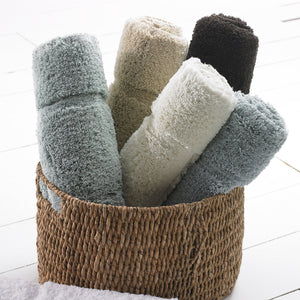 Rolled cotton bath rugs / bath mats in a wicker basket