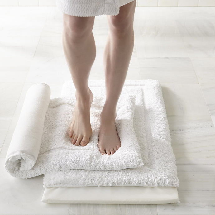 woman standing on white memory foam bath rug