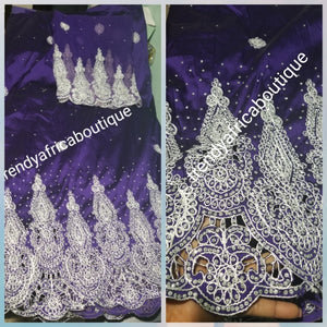 Original quality taffeta George wrapper. beautiful Purple embrioded and all over crystal stones Wrapper in 5yds + 1.8yds net for blouse. dazzling crystal stones to perfection. Small-George. Model wearing similar George. Use for Nigerian weddings and more