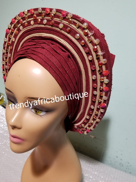 Wine/champagne aso-oke embellished with beads/stones auto-gele. Wahala free gele already made for you with finest quality aso-oke. Easy adjustment for proper fit at the back. Original quality from Nigeria.