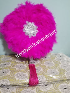 fluffy feather hand fan in beautiful fuchsia pink feathers, embellished with silver accessories. Nigerian traditional Bridal Accessories hand fan for celebrant. Fully handmade with silver handlel & matching pink tassels. Round fluffy feathers hand fan