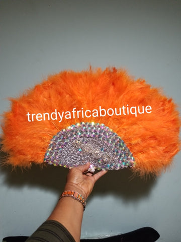 "New arrival Orange Feather hand fan. Medium size moon shape hand fan Nigerian  Bridal-accessories front and back  design with gold beads and flower petal. Limited quantity. 19"" long + 14"" wide. Small handle to hold your fan. Very classy"