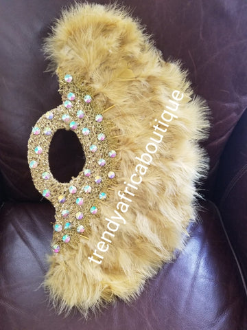 "New arrival Pure Gold  feather hand fan. Large moon shape with handle. Nigerian  Bridal-accessories flower brooch front design. Embellished with sparkling crystal stones.. 25"" long + 14"" wide. Small handle to hold your fan."