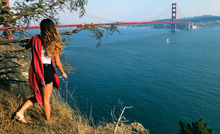 audris peering around kirby cove to see sunset at the golden gate bridge with the red manhattan beach towel