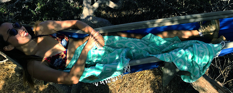 audris relaxing in a hammock after a hike in catalina on the green mykonos helix towel