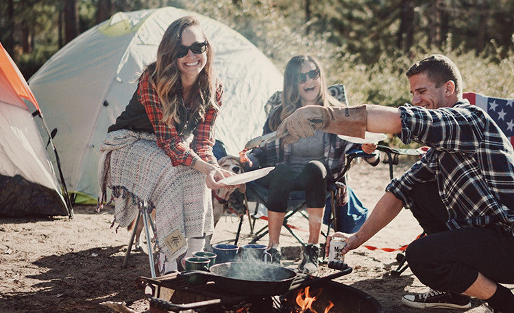 Alexa, Monet, and Tyler cooking breakfast around the campfire with their Gray Manhattan Beach Helix Towel