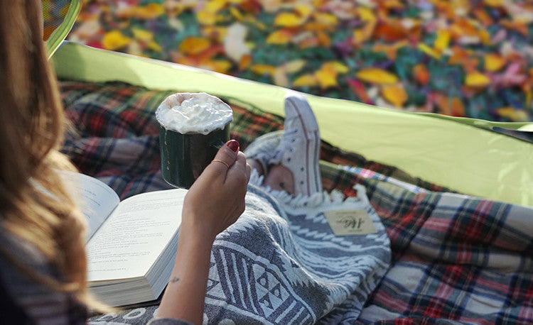 monet sipping hot chocolate and reading in her tent with her Black Machu Picchu Helix Towel