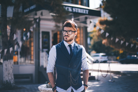A young man with a well groomed beard in public.