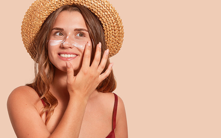 Attractive smiling woman applying sunscreen