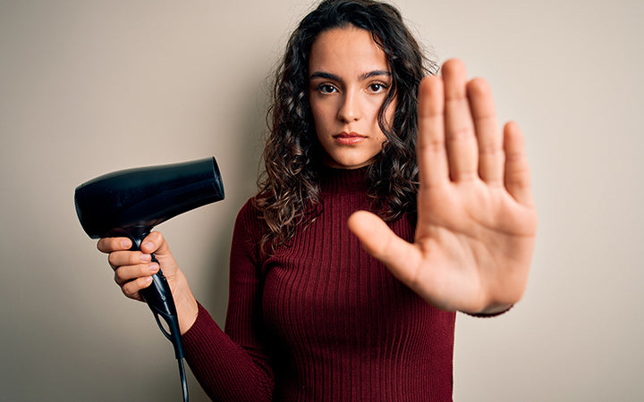 Beautiful woman with curly hair using hair dryer