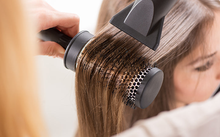 Drying long brown hair with hair dryer and round brush