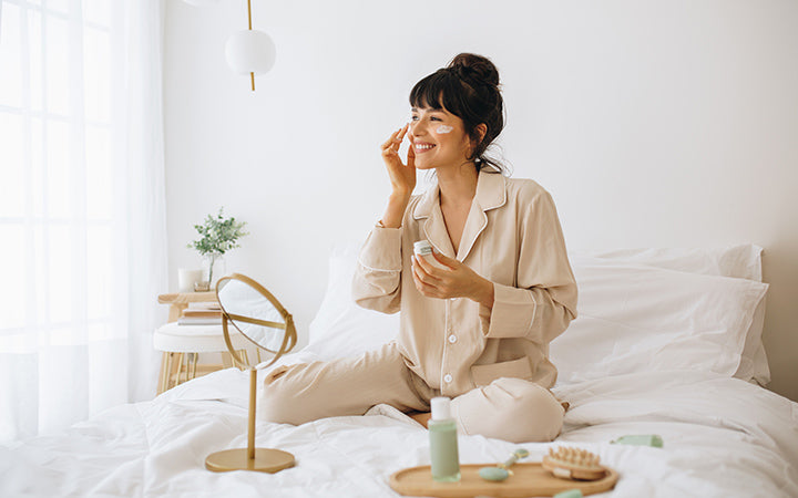 Happy woman doing routine skin care at home with beauty products