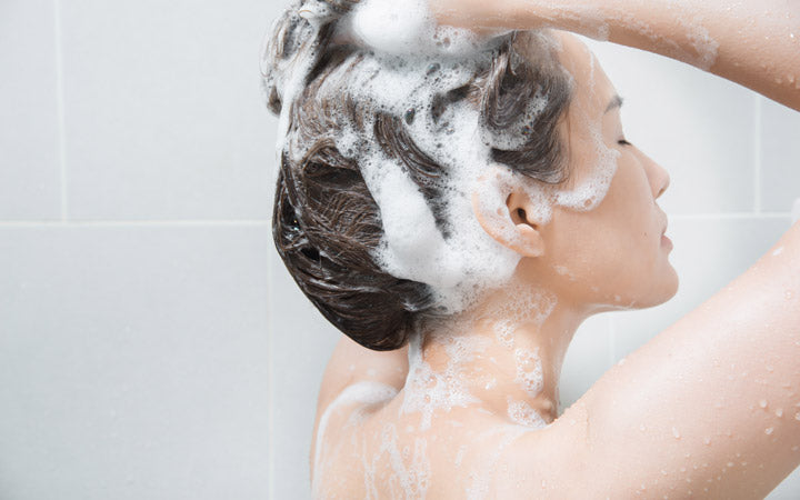 Woman shampooing to scalp