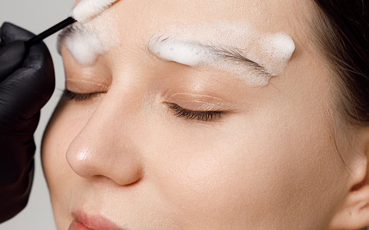 Master applies brow paste with a brush to eyebrows