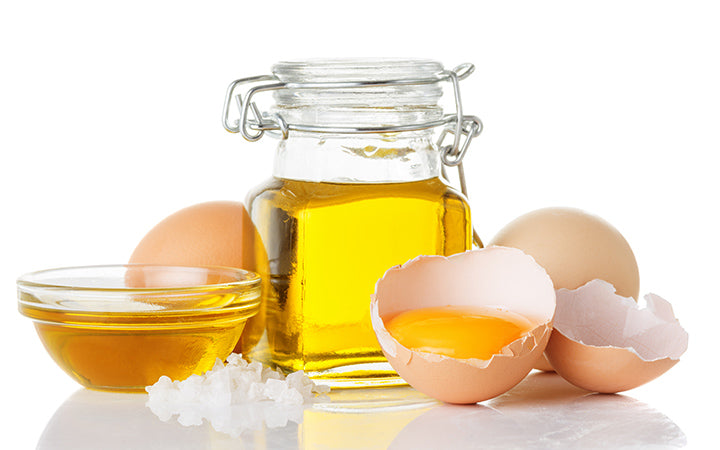 Natural ingredients like olive oil in a bottle and raw eggs for hair