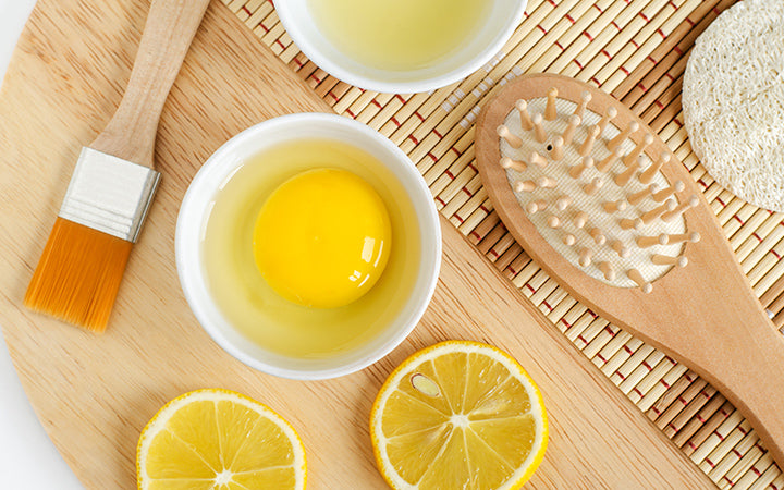 Raw egg in the small white bowl, lemon juice and slices