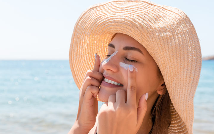 Smiling woman hat applying sunscreen