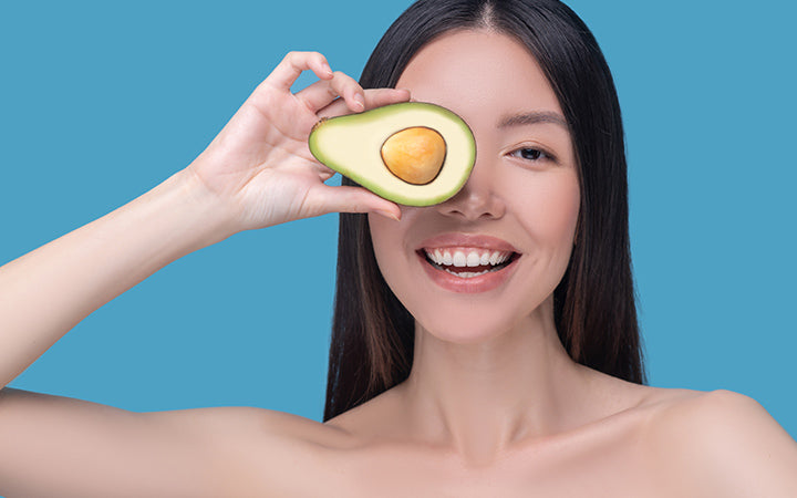 Smiling young asian woman holding avocado