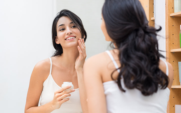 Woman caring of her beautiful skin on the face standing near mirror applying moisturizer on her face