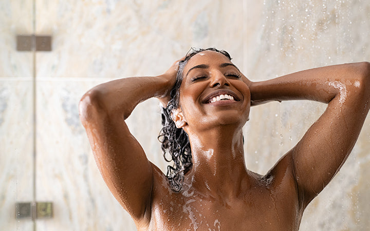 Woman washing her curly hair with shampoo and a lot of lather