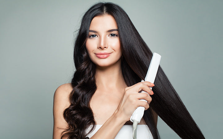 Woman with curly hair and long straight hair using hair straightener