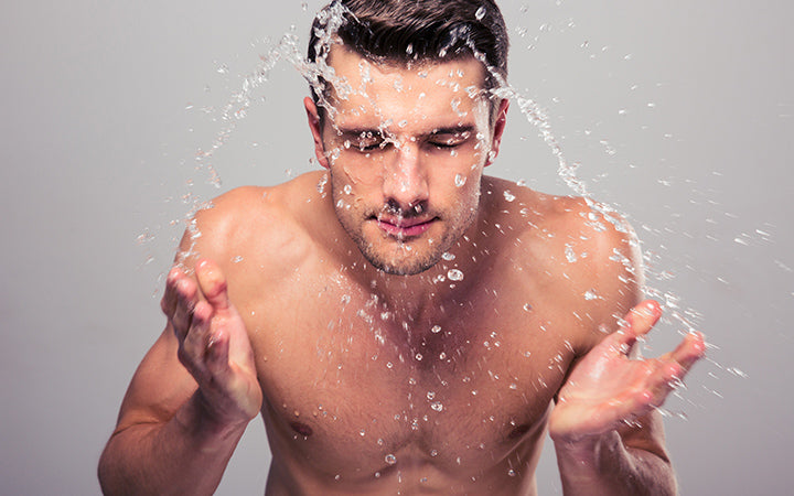 Young man spraying water on his face