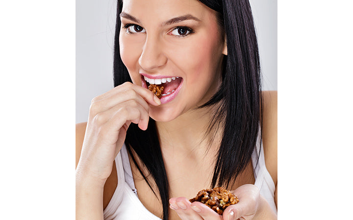 Young woman eating shelled nuts