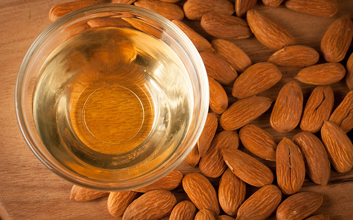 almonds and almond oil on wooden background