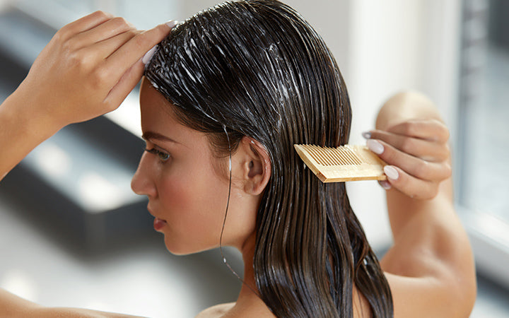 Beautiful woman hairbrushing with comb and using conditioner