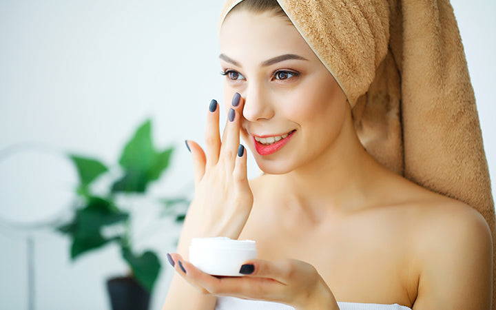 beautiful woman using a skin care product moisturizer or lotion