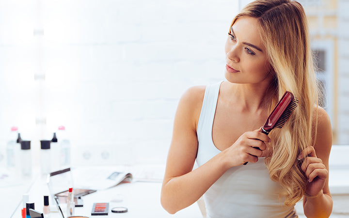 beautiful young woman looking at her reflection in mirror and brushing her long hair for getting rid of tangles