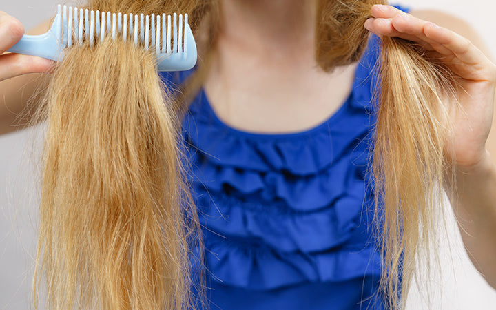 blonde woman with comb brushing her very long messy hair