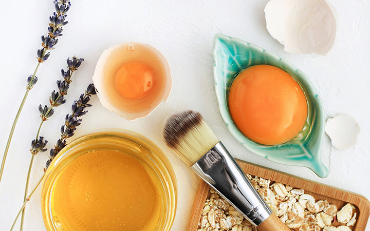 bright egg yolks, oatflakes, honey, lavender with cosmetic brush closeup, natural holistic ingredients for homemade beauty care