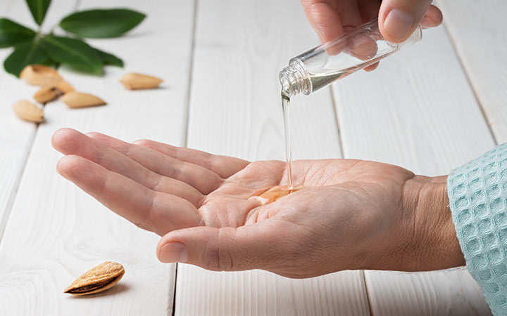 female hands while applying natural almond essential oil
