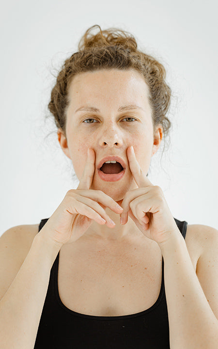 girl doing face yoga exercises stretching and strengthening the muscles of the face