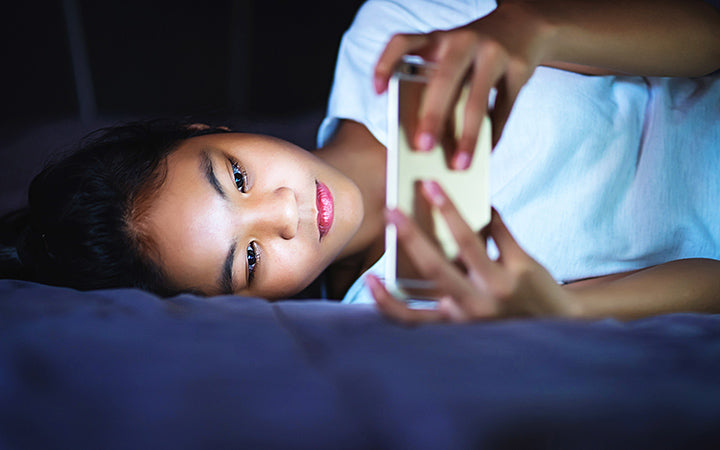 girl lying in bed at night and using smart phone