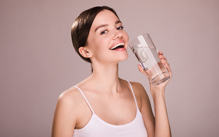happy young woman smiling by holding glass of water