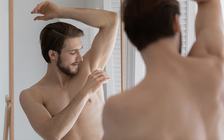 mirror reflection young man applying antiperspirant on armpit after shower