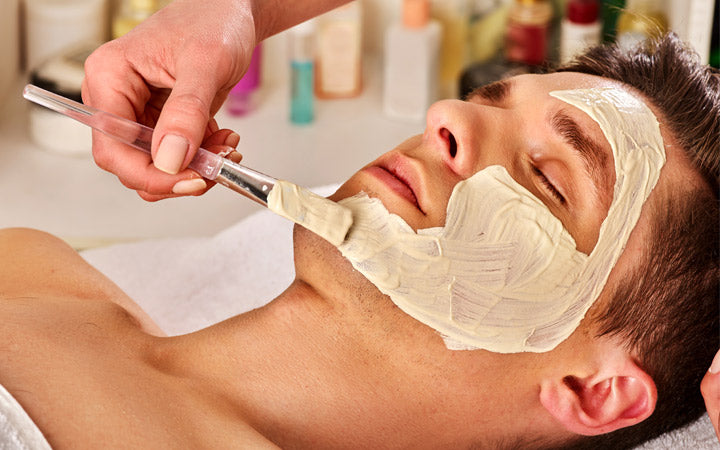mud facial mask of man in spa salon