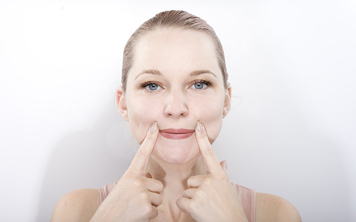 the girl does massage and rejuvenating exercises for the face