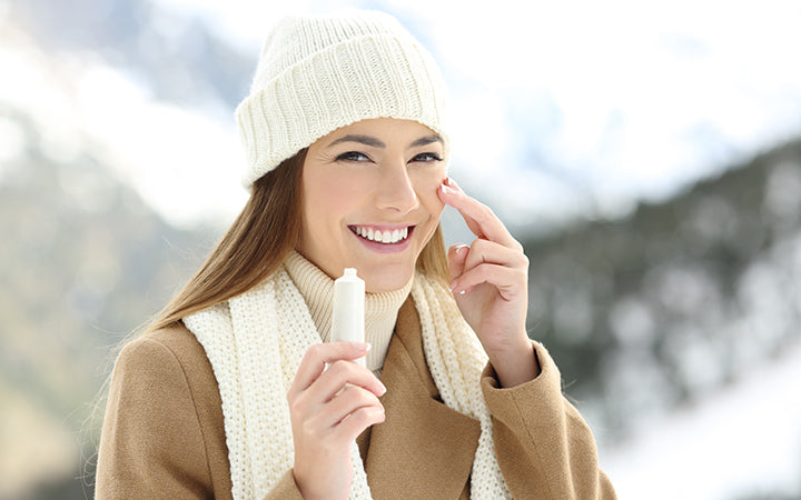 woman applying moisturize cream in face with a snowy mountain in the background