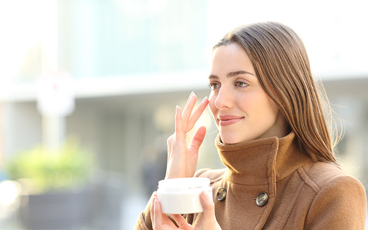 woman applying mousturizer cream on her face in winter in the street