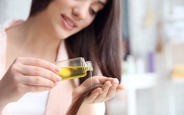 woman applying oil onto hair at home