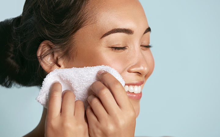 woman cleaning facial skin with towel after washing face