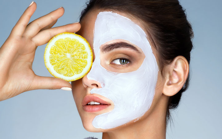 woman holding a slice of lemon in front of her face