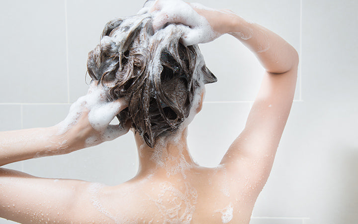 woman in shower washing hair with shampoo